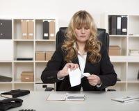 撕毁文件的年轻女实业家 免版税库存照片
