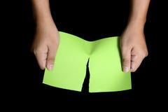 撕毁绿皮书的手 库存照片
