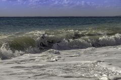撞入海滩的硕大绿松石膨胀在一个天空蔚蓝夏日在西西里岛 图库摄影