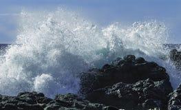 撞入黑熔岩峭壁的硕大绿松石膨胀在一个天空蔚蓝夏日在西西里岛 免版税库存照片