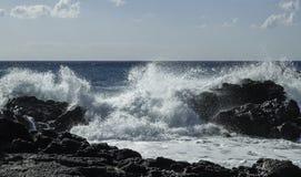 撞入黑熔岩峭壁的硕大绿松石膨胀在一个天空蔚蓝夏日在西西里岛 库存照片