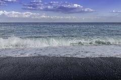 撞入黑pebbled海滩的绿松石膨胀在一个天空蔚蓝夏日在西西里岛 免版税库存照片