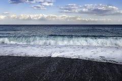 撞入黑pebbled海滩的膨胀在西西里岛 库存图片