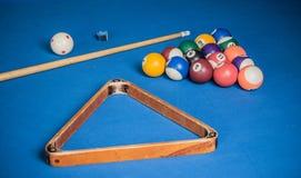 撞球、暗示和白垩在一个蓝色撞球台上 免版税库存图片