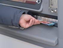 撤出从ATM的金钱的人的手 免版税库存图片