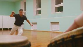 播放一两个乐器jembe或atabaque在背景男性战斗机执行军事把戏与舞蹈 影视素材