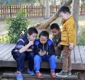 播放一个新的电话的小男孩 免版税库存照片