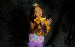 播放一个黄色小手鼓的女孩 库存照片