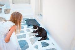 播放一只猫的小可爱的女孩特写镜头在希腊村庄,米科诺斯岛,希腊 免版税库存照片