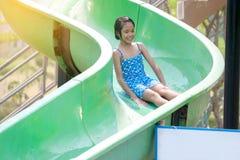 播放一张幻灯片的亚裔女孩在水公园 库存图片