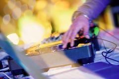 播放与轻和模糊的bokeh的DJ的移动的手的特写镜头行动转盘在背景中 图库摄影