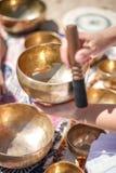 播放唱歌的亦称妇女滚保龄球西藏人唱歌碗,喜马拉雅碗 做合理的按摩 图库摄影