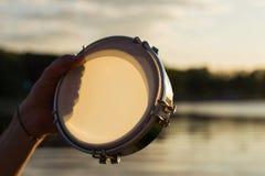 播放在背景天空的一个乐器小手鼓在日落 免版税图库摄影