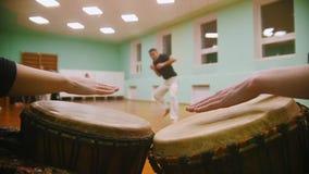播放在背景男性战斗机的一两个乐器jembe执行军事把戏与舞蹈元素 股票录像