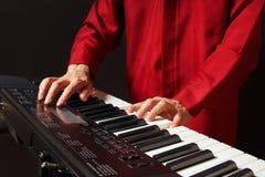 播放在黑背景的钢琴演奏家电子口琴 免版税库存照片