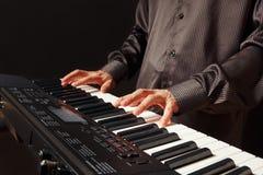 播放在黑背景的钢琴演奏家synth 免版税库存图片