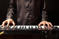 播放在黑背景的音乐家合成器 免版税图库摄影