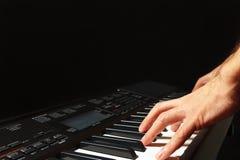 播放在黑背景的音乐家的手合成器 免版税图库摄影