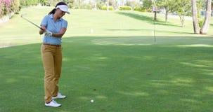 播放在绿色的一个冲程的女子高尔夫球运动员 免版税库存照片