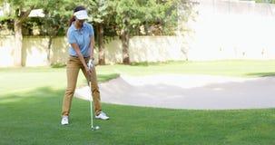 播放在绿色的一个冲程的女子高尔夫球运动员 库存图片
