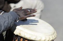 播放大鼓声的音乐家的手 库存图片