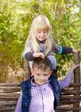 播放她的兄弟的头发的逗人喜爱的白肤金发的女孩 库存图片