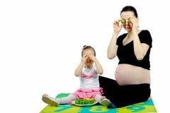 播放对她怀孕的母亲的被隔绝的第一个孩子用果子 免版税库存图片