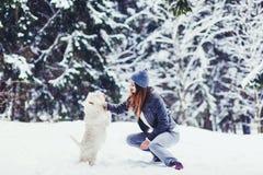 播放对她的狗的愉快的美丽的年轻女人 图库摄影