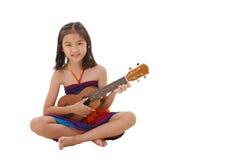 播放尤克里里琴的礼服的小女孩 免版税图库摄影