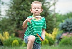 播放比赛投掷的圆环的逗人喜爱的男孩户外在夏天公园 胜利喜悦  库存图片