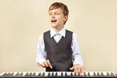 播放电子口琴的衣服的年轻滑稽的男孩 免版税图库摄影