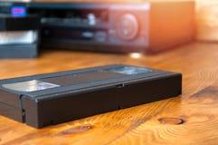播放的VHS录音带设备在一张木桌上 免版税库存图片