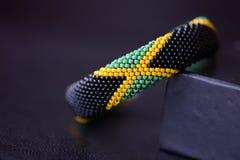 播种在黑暗的背景的小珠镯子牙买加旗子 免版税库存图片