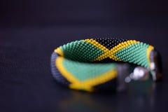 播种在黑暗的背景的小珠镯子牙买加旗子 库存图片