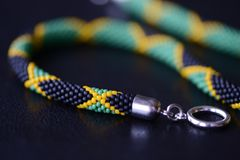 播种在黑暗的背景的小珠项链牙买加旗子 免版税库存图片