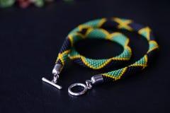 播种在黑暗的背景的小珠项链牙买加旗子 库存照片