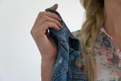 播种拿着一条牛仔裤的观点的年轻成人白肤金发的妇女 库存图片
