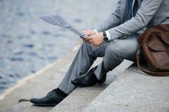 播种的观点的在灰色衣服读书报纸的商人 免版税库存照片