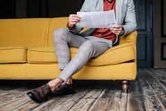 播种的观点的时髦的人坐有报纸的长沙发 库存照片