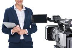 播种的观点的有站立在照相机前面的数字式片剂的新闻广播员, 免版税库存图片