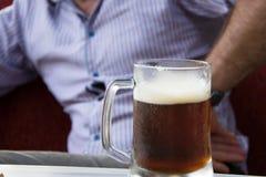 播种的观点的衬衣的可爱的人有在桌上的啤酒杯的 库存图片