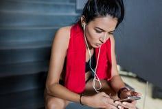 播种紧密运动的可爱的深色的女性画象有红色毛巾的在脖子在健身房的锻炼以后坐台阶 库存照片