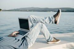 播种年轻人自由职业者照片与坐n的膝上型计算机一起使用 库存图片
