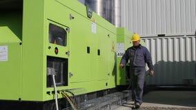 操作两台强有力的柴油发电器供应沥青拌和楼的工作者 股票视频