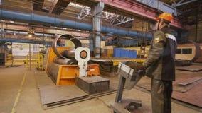 操作员控制加工弯曲的金属板到管在植物 股票视频