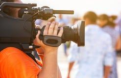 操作员摄影师承担一台专业照相机采访 图库摄影