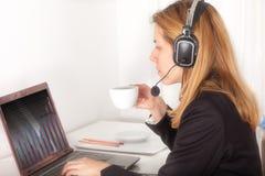 操作员用电话耳机饮用的咖啡 免版税库存照片