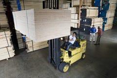 操作在木材产业的工作者一辆叉架起货车 免版税库存照片