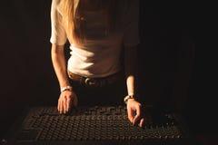 操作混音器的女性DJ的中间部分 免版税库存图片