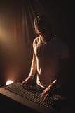 操作混音器的男性DJ在音乐音乐会 免版税库存图片